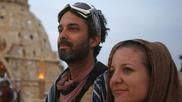 "Dan Parras, left, and Melissa Bauman wait for the sun to rise at the Temple of Grace during the Burning Man 2014 ""Caravansary"" arts and music festival in the Black Rock Desert of Nevada"