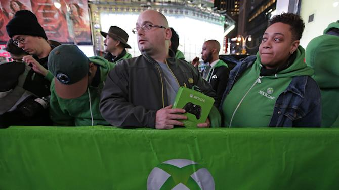 FILE - In this Thursday, Nov. 21, 2013, file photo, people line up outside the Best Buy Theater in Times Square awaiting the opportunity to purchase Microsoft's Xbox One video gaming console at a midnight sales launch, in New York. Microsoft reports quarterly earnings on Thursday, Jan. 23, 2014. (AP Photo/Kathy Willens, File)