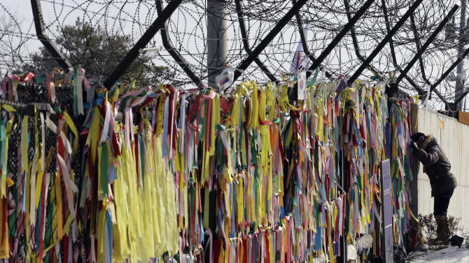 A man looks through the wire fence covered with ribbons carrying messages of people's wish for the reunification of the two Koreas at the Imjingak Pavilion near the border village of Panmunjom, which has separated the two Koreas since the Korean War, in Paju, north of Seoul, South Korea, Wednesday, Feb. 13, 2013. Defying U.N. warnings, North Korea on Tuesday conducted its third nuclear test in the remote, snowy northeast, taking a crucial step toward its goal of building a bomb small enough to be fitted on a missile capable of striking the United States. (AP Photo/Lee Jin-man)