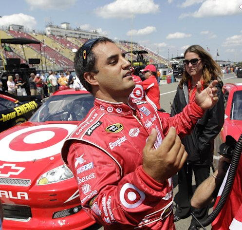Juan Pablo Montoya talks with a crew member after winning the pole during qualifying for the NASCAR Sprint Cup Series race at Watkins Glen International in Watkins Glen, N.Y., Saturday, Aug. 11, 2012. (AP Photo/David Duprey)