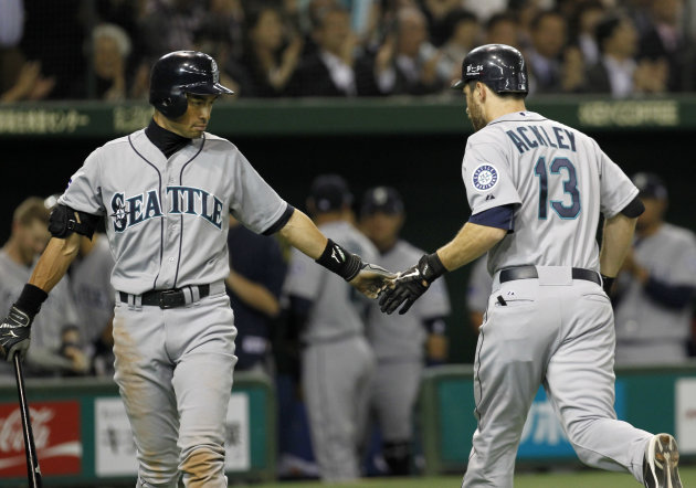 Seattle Mariners&#39; Dustin Ackley (13) is congratulated by teammate Ichiro Suzuki at home after hitting a solo shot against Oakland Athletics starter Brandon McCarthy in the fourth inning of their American League season opening MLB baseball game at Tokyo Dome in Tokyo, Wednesday, March 28, 2012. in Tokyo, Wednesday, March 28, 2012. (AP Photo/Koji Sasahara)