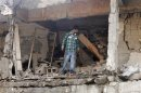 A man walks among the ruins of a damaged building at the site of a blast in the town of Reyhanli