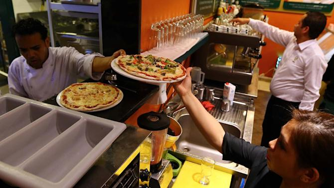 An employee serves a pizza at a cafe in the Libyan capital Tripoli, on August 21, 2014