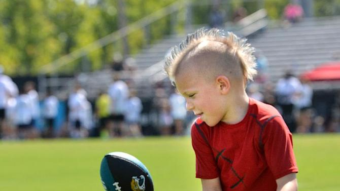Hunter Hoffman, 7, almost catches a pass during one of the drills at an NFL football Jacksonville Jaguars' Got Skills Rookie Day on Friday, June 20, 2014, in Jacksonville, Fla
