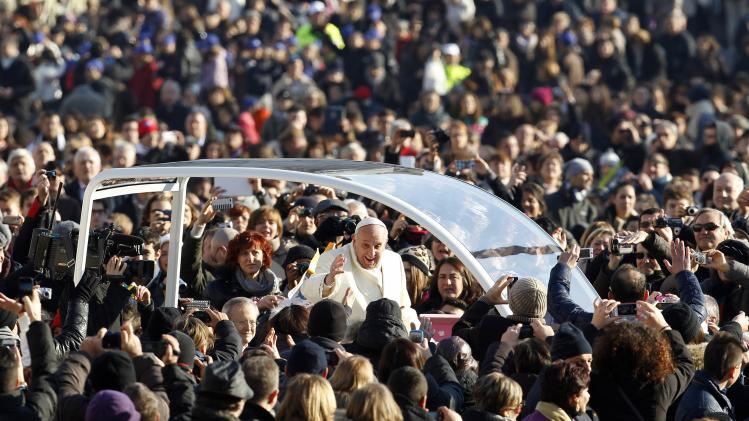 Pope Francis waves as he arrives to conduct his weekly general audience at St. Peter's Square at the Vatican