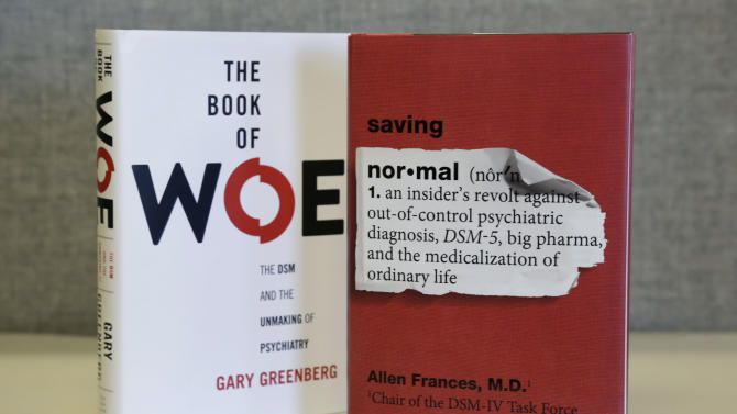 """This Monday, May 13, 2013 photo shows the books """"The Book of Woe"""" by Gary Greenberg and """"Saving Normal"""" by Allen Francis on display in Chicago. Recent criticism of changes in an update of psychiatry's most widely used guidebook for diagnosing mental illness include these books by two respected therapists. They argue that the American Psychiatric Association's guidebook is turning normal human conditions into mental illness and will lead to even more overuse of psychiatric drugs. The association is introducing the updated guide at its annual meeting in San Francisco in May 2013. (AP Photo/M. Spencer Green)"""