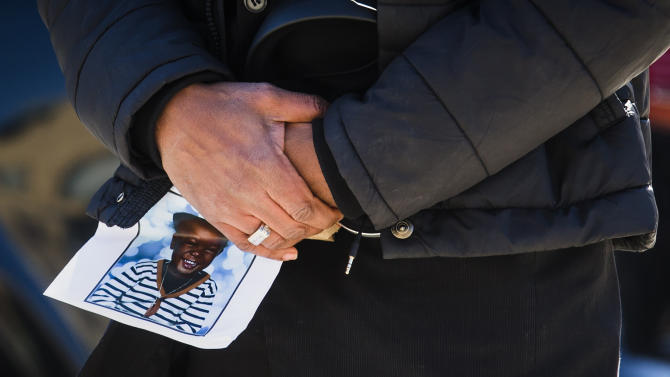 A man holds a picture of three-year-old Elijah Marsh during his funeral in Toronto