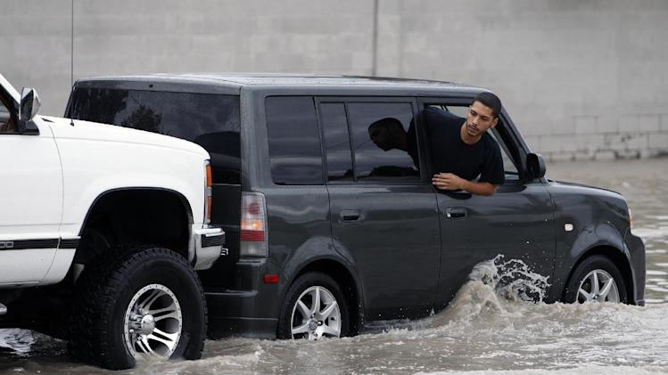 A man peers out of a stalled car in floodwater on Sahara Avenue at Abarth Street in Las Vegas on Wednesday, Aug. 22, 2012. Heavy rains caused flooding as intense thunderstorms filled storm channels and sent water into roadways. (AP Photo/Las Vegas Review-Journal, John Locher) LOCAL TV OUT; LOCAL INTERNET OUT; LAS VEGAS SUN OUT