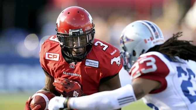 Calgary Stampeders' Fuller braces himself for a tackle from Montreal Alouettes' Hefney during their CFL football game in Calgary
