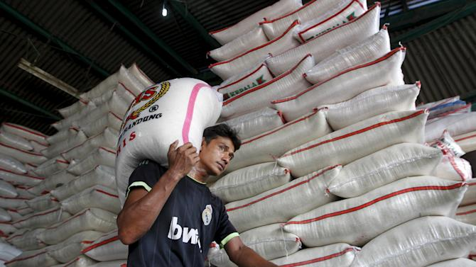 A worker carries a sack of rice at a wholesale rice market in East Jakarta