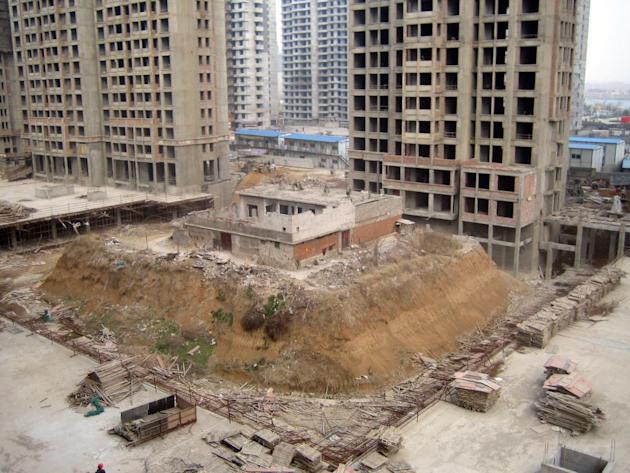 A couple's home in  Zaozhuang, northern China's Shandong Province has been left on its own isolated 'island' after real estate developers dug out the ground around it.  The couple, who