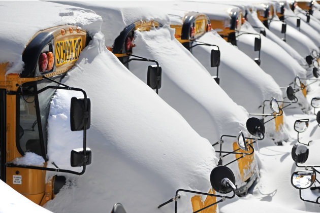 School buses are covered in snow after a winter storm in Hartford, Conn., Sunday, Feb. 10, 2013. A howling storm across the Northeast left much of the New York-to-Boston corridor covered with more tha