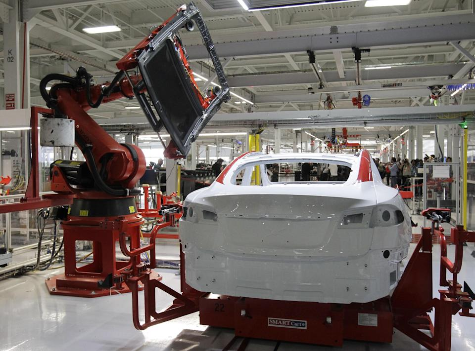 A robot puts on the top of a Tesla Model S at the Tesla factory in Fremont, Calif., Friday, June 22, 2012. The first Model S sedan car will be rolling off the assembly line on Friday.  (AP Photo/Paul Sakuma)