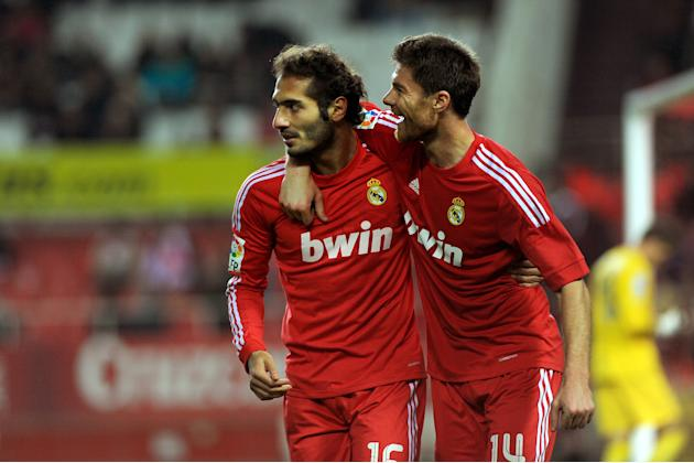 Real Madrid's midfielder Turkish Hamit Altintop (L) celebrates with midfielder Xabi Alonso (R) after scoring during their Spanish league football match Sevilla FC vs Real Madrid on December 17, 2011 a