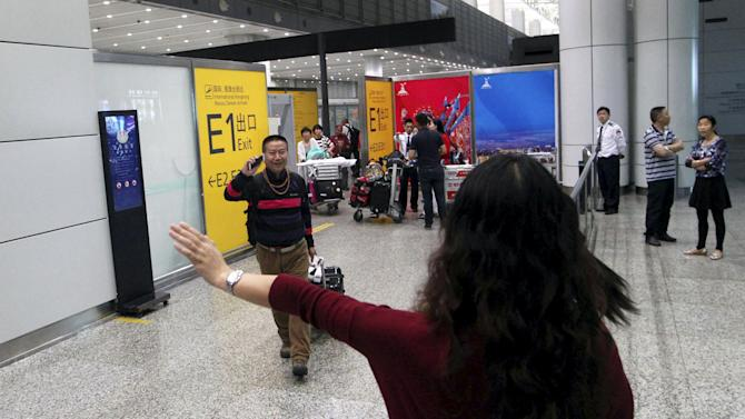 A woman waves to her relative after he came back from Kathmandu after a 7.9-magnitude earthquake hit Nepal on Saturday, in Guangzhou