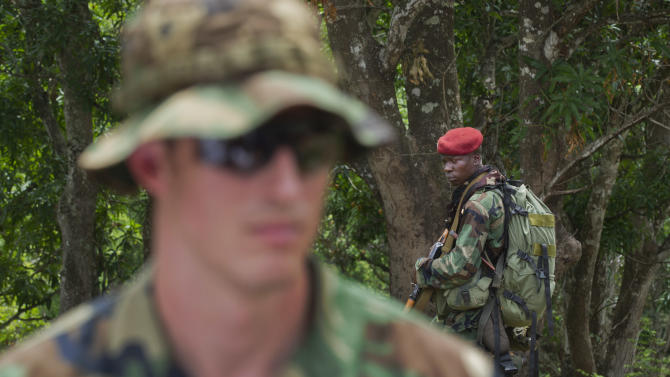 A soldier from the Central African Republic, right, looks across as U.S. Army special forces Captain Gregory, 29, from Texas, left, who would only give his first name in accordance with special forces security guidelines, speaks with other troops from the Central African Republic and Uganda, where they are searching for infamous warlord Joseph Kony, in Obo, Central African Republic, Sunday, April 29, 2012. Obo was the first place in the Central African Republic that Joseph Kony's Lord's Resistance Army (LRA) attacked in 2008 and today it's one of four forward operating locations where U.S. special forces have paired up with local troops and Ugandan soldiers to seek out Kony and hope he will stand trial at the International Criminal Court for war crimes and crimes against humanity after his forces cut a wide and bloody swath across several central African nations. (AP Photo/Ben Curtis)