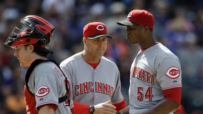 Cincinnati Reds pitching coach Byan Price, center, talks with relief pitcher Aroldis Chapman (54) as catcher Ryan Hanigan, left, returns to the mound during the eighth-inning of the Reds' 9-4 loss to the New York Mets in their baseball game at Citi Field in New York, Thursday, May 17, 2012. (AP Photo/Kathy Willens)