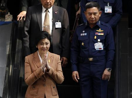 Thailand's PM Yingluck gestures as she leaves the Royal Thai Air Force Headquarters in Bangkok