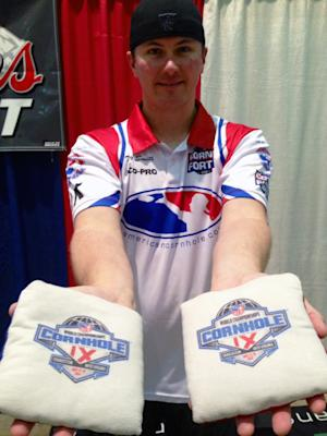 Toby Smith of Blacksburg, Va., poses for a photo as he holds bags used in competition at the World Championships of Cornhole tournament on Friday, July 18, 2014, in Charleston, W. Va. The tournament that crowns winners in singles and doubles events continues through Saturday. (AP Photo/John Raby)