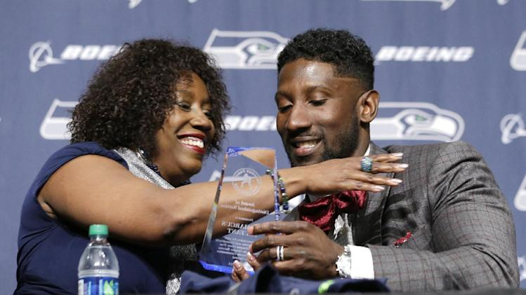 Seattle Seahawks' Marcus Trufant, left, is embraced by his mother, Constance Trufant, as she presented him with an award from the Trufant Family Foundation at a news conference announcing his retirement from football after signing with the team a day earlier, Thursday, April 24, 2014, in Renton, Wash. Trufant started 125 games in a Seattle career that lasted from 2003 to 2012. The cornerback was a first-round pick in 2003 out of Washington State and immediately moved into the starting lineup, playing a key role on the 2005 team that advanced to the franchise's first Super Bowl