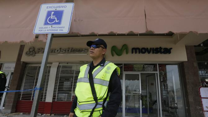 Federal police officer stands guard outside stores that were damage and looted in San Jose del Cabo