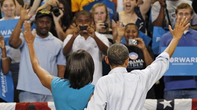 President Barack Obama and first lady Michelle Obama wave to the crowd during a campaign rally at Virginia Commonwealth University in Richmond, Va., Saturday, May 5, 2012. (AP Photo/Steve Helber)