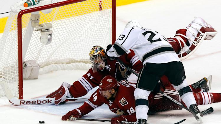 Phoenix Coyotes' Rostislav Klesla (16), of the Czech Republic, and Mike Smith, both dive to block the shot of Los Angeles Kings' Dustin Brown (23) during the first period of Game 1 of the NHL hockey Stanley Cup Western Conference finals, Sunday, May 13, 2012, in Glendale, Ariz.(AP Photo/Ross D. Franklin)