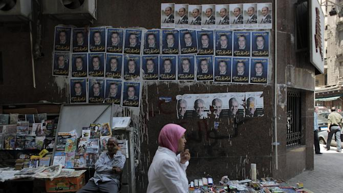 """A woman walks past a street vendor sitting under electoral posters with pictures of presidential candidates Khaled Ali, top row, Aboul Ezz el-Hariri, center, and Hamdeen Sabahi, with Arabic writing which reads  """"The Revolution Continues""""  in Cairo, Egypt, Monday, May 7, 2012. The first round of presidential elections is set for May 23-24. (AP Photo/Nasser Nasser)"""