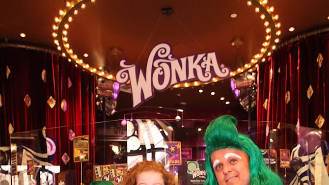 IMAGE DISTRIBUTED FOR WONKA - Francesca Capaldi, center, is seen with Wonka's Oompa Loompas at the new Wonka store at Sweet! Hollywood during the launch of the Wonka Inventing Room Collection, a decadent premium chocolate line, on Tuesday Nov. 13, 2012, in Los Angeles. (Photo by Casey Rodgers/Invision for WONKA/AP Images)