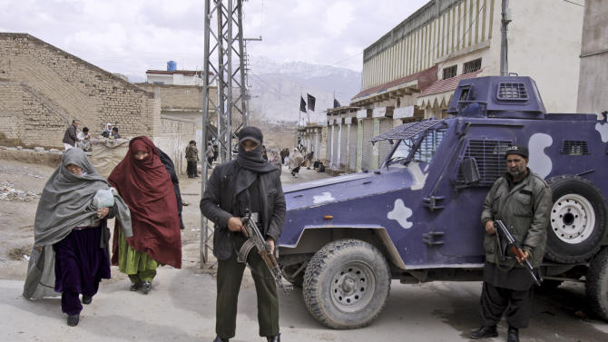 """In this Friday, Feb. 22, 2013, photo, Pakistani security men stand alert as women from Pakistani Hazara Shiite community walk past, during Friday prayers outside a Shiite mosque,  in Quetta, Pakistan. Pakistan's minority Shiite Muslims have begun to use words like """"genocide"""" to describe a violent spike in attacks directed against them by a militant Sunni group, with suspicious links to the country's security agencies and a mainstream political party that governs the largest province, where some of the most violent jihadi groups are headquartered. (AP Photo/Arshad Butt)"""