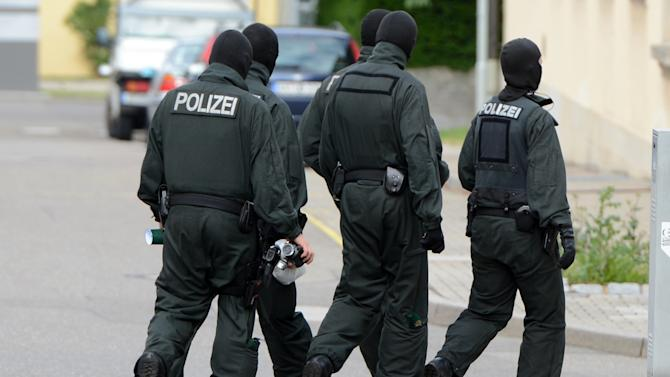 Members of a special response unit of the German state police leave the site of a search operation in Fellbach, Germany, Tuesday, June 25, 2013, as German prosecutors said they are investigating two men suspected of planning terrorist attacks using model airplanes. Authorities in Germany and neighboring Belgium conducted a series of searches of nine properties in Germany and Belgium. (AP Photo/dpa, Franziska Kraufmann)