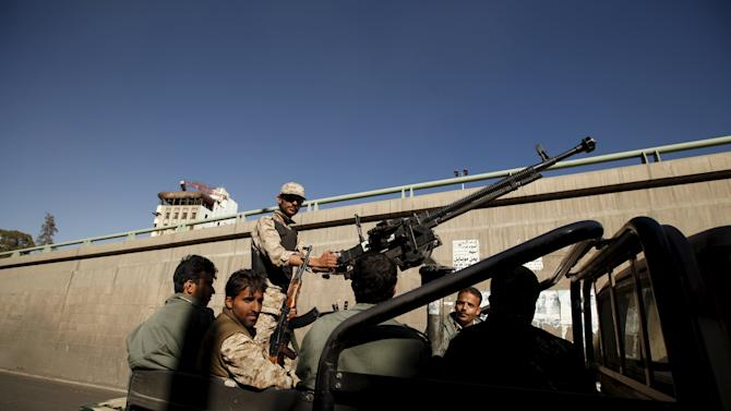 Houthi militants ride on the back of a patrol truck as they secure the site of a rally commemorating the anniversary of South Yemen's independence from British colonial rule, in Yemen's capital Sanaa