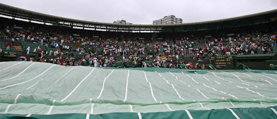 Ground keepers pull on a cover as rain interrupts play between Andy Roddick of the United States and Jamie Baker of Britain during a first round men's singles match at the All England Lawn Tennis Championships at Wimbledon, England, Tuesday, June 26, 2012. (AP Photo/Tim Hales)