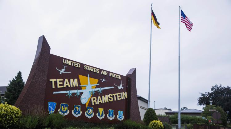 The flags of the United States and Germany fly behind a sign at Ramstein Air Base