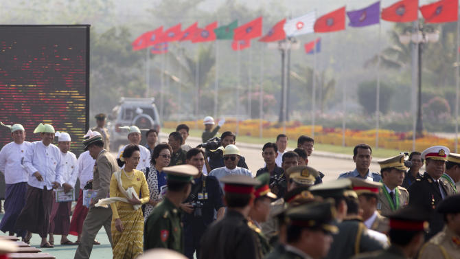 Opposition leader Aung San Suu Kyi, in yellow leaves after attending Myanmar's 68th anniversary celebrations of Armed Forces Day, in Naypyidaw, Myanmar, Wednesday, March 27, 2013. The daughter of Aung San, Myanmar's most famous general and founding father, Suu Kyi has reached out to the military which was known for its brutality during its half-century of absolute rule over the objections of some in her own party. (AP Photo/Gemunu Amarasinghe)