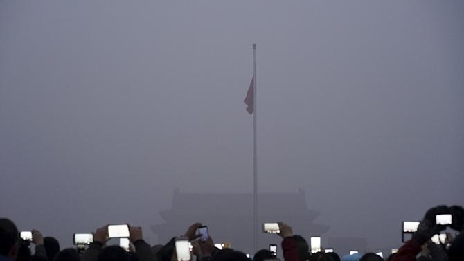 Visitors uses mobile phones to take pictures and videos as they watch a flag raising ceremony at the Tiananmen Square amid heavy smog in Beijing