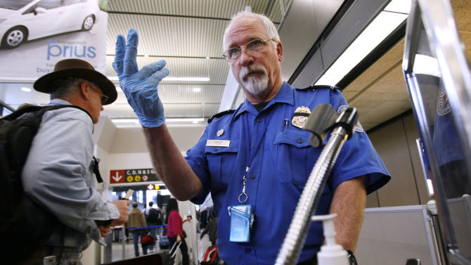 FILE - In this Jan. 4, 2010 file photo, TSA officer Robert Howard signals an airline passenger forward at a security check-point at Seattle-Tacoma International Airport in SeaTac, Wash. The head of the Transportation Security Administration on Thursday, March 14, 2013 told lawmakers he stands by his plan to allow passengers to carry small knives onto planes despite a growing backlash against the proposal. (AP Photo/Elaine Thompson, File)