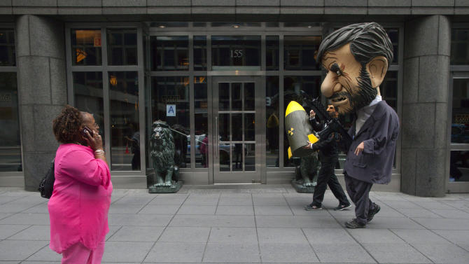 A woman looks as two men dressed as Iranian leader Ahmadinejad walk toward a protest on the sidelines of the UN General Assembly in New York