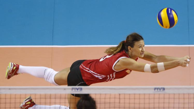 Ozsoy of Turkey dives to receive the ball during their FIVB Women's Volleyball World Grand Prix 2014 final round match against China in Tokyo