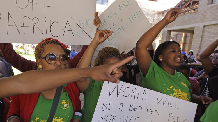 Students protest outside a hall were U.S. Secretary of State, Hillary Rodham Clinton, spoke in Cape Town, South Africa, Wednesday, Aug. 8, 2012. South Africa must live up to the legacy left by freedom icon Nelson Mandela by promoting human rights and democracy among its neighbors and around the world, U.S. Secretary of State Hillary Rodham Clinton said Wednesday. (AP Photo/Schalk van Zuydam)