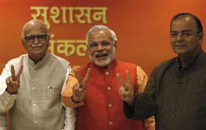 India's BJP leader Advani, Gujarat's CM Modi and leader Jaitley show victory signs in New Delhi