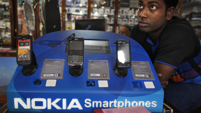 FILE- In this Thursday, June 14, 2012, file photo, an Indian shopkeeper selling Nokia mobile phones awaits customers in New Delhi, India.  Nokia's net loss more than tripled in the second quarter the company reported Thursday July 19, 2012.  (AP Photo/Tsering Topgyal, File)