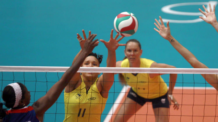 Cuba's Kenia Carcases Opon, left, spikes the ball against Brazil's Tandara Caixeta, center, in the women's volleyball gold medal match during the Pan American Games in Guadalajara, Mexico, Thursday, Oct. 20, 2011.(AP Photo/Dario Lopez-Mills)
