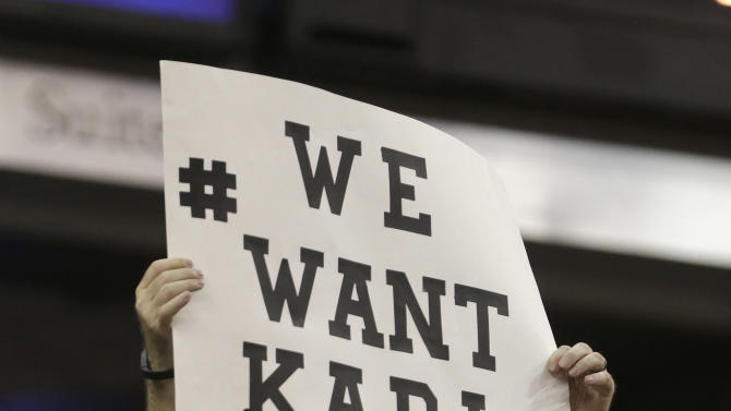 A Sacramento Kings fan displays a sign calling for former NBA head coach George Karl to take over as coach of the Kings, during the second half of the Kings 108-101 win over the Los Angeles Lakers in an NBA basketball game in Sacramento, Calif., Sunday, Dec. 21, 2014. Former Kings coach Michael Malone was fired last week and Tyrone Corbin is currently the interim head coach of the team.(AP Photo/Rich Pedroncelli)