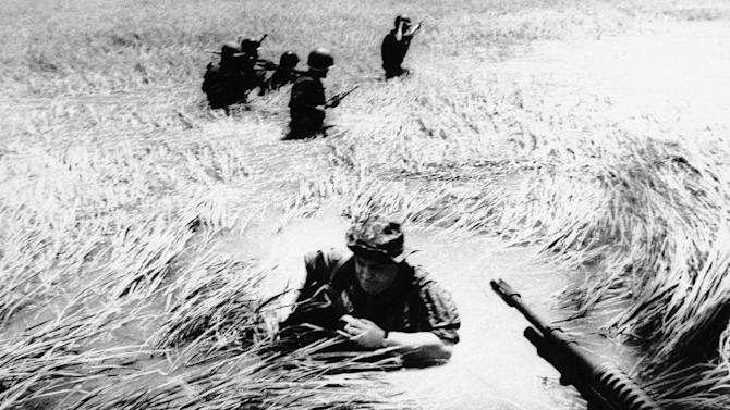 FILE - In this May 11, 1965 file photo, Associated Press photographer Horst Faas tries to get back on a U.S. helicopter after a day out with Vietnamese rangers in a flooded plain of reeds. Faas, a prize-winning combat photographer who carved out new standards for covering war with a camera and became one of the world's legendary photojournalists in nearly half a century with The Associated Press, Thursday May 10, 2012. He was 79. (AP Photo/File)