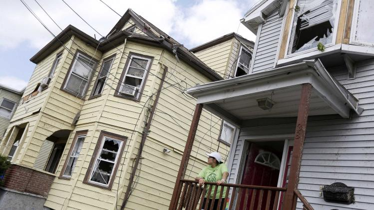 A woman looks at her neighbours' properties from her porch on Taft Street in Revere, Massachusetts