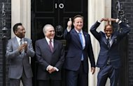 British double olympic gold medal winner Mo Farah (R) does the 'Mobot' as he poses for pictures with Former Brazilian footballer Pele, (L) Vice-President of Brazil Michel Temer, (2nd L) and British Prime Minister David Cameron (2nd R) outside 10 Downing Street in London