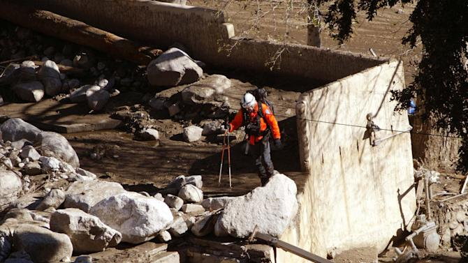FILE - In this Saturday, Dec. 27, 2003, file photo, a rescue worker searches for victims after devastating mudslides swept through the Waterman Canyon area of the San Bernardino, Calif., mountains two days earlier. Fourteen people — including nine children — were killed in 2003 when a wave of water, boulders and debris tore through a campground in the foothills of San Bernardino east of Los Angeles. A decade later, painful memories still remain. (AP Photo/Nick Ut, File)