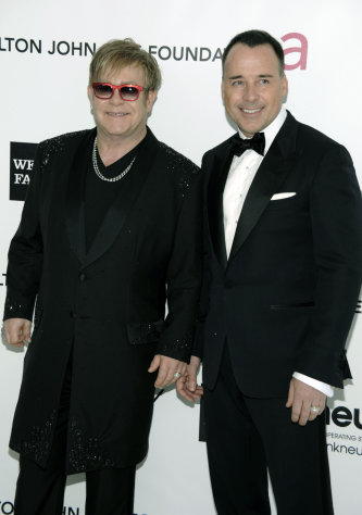 FILE - In this Feb. 26, 2012 file photo, Elton John, left, and David Furnish arrive at the Elton John AIDS Foundation Academy Awards viewing party in West Hollywood, Calif. Elton John has raised $125 million for his AIDS foundation through various galas he hosts, including his famous Grammy and Oscar parties. (AP Photo/Dan Steinberg, File)
