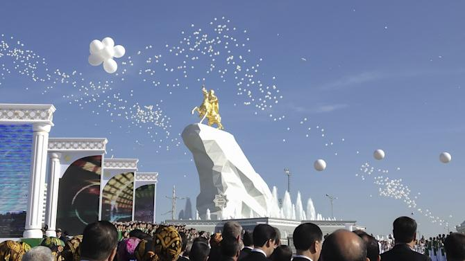 People gather in front of a monument to Turkmenistan's President Kurbanguly Berdymukhamedov during its inauguration ceremony in Ashgabat